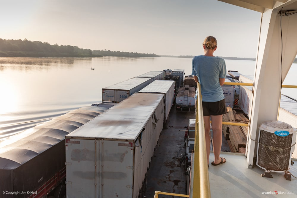 Sheri on a barge in the Amazon River looking out over cargo trucks